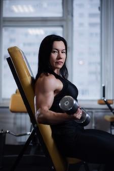 Chica fitness entrena bíceps con pesas en el gimnasio.