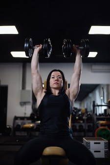 Chica fitness entrena con pesas en el gimnasio
