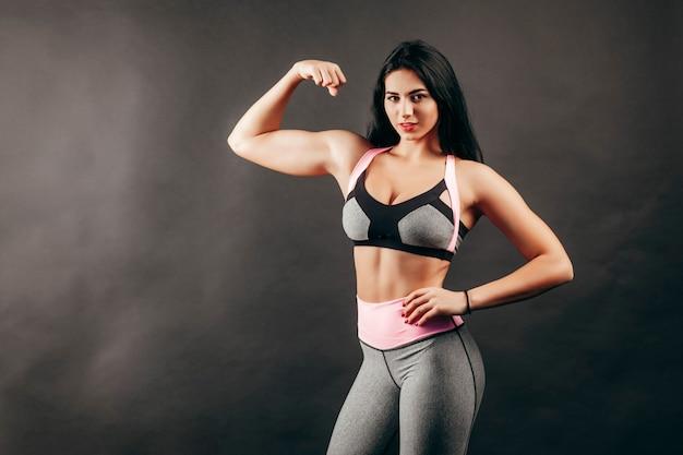Chica fitness fuerte muestra músculo en el estudio