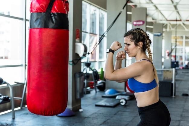 Chica fitness golpeando saco de boxeo