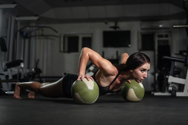 Chica fitness hace flexiones en la pelota