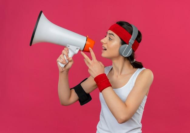 Chica fitness joven disgustado en ropa deportiva con diadema y auriculares gritando al megáfono parado sobre pared rosa