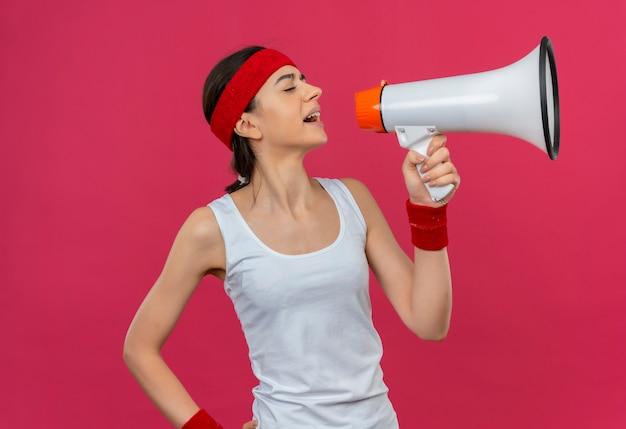 Chica fitness joven frustrada en ropa deportiva con diadema gritando al megáfono parado sobre la pared rosa