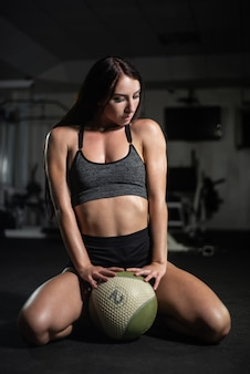 Chica fitness posa con una pelota en el gimnasio