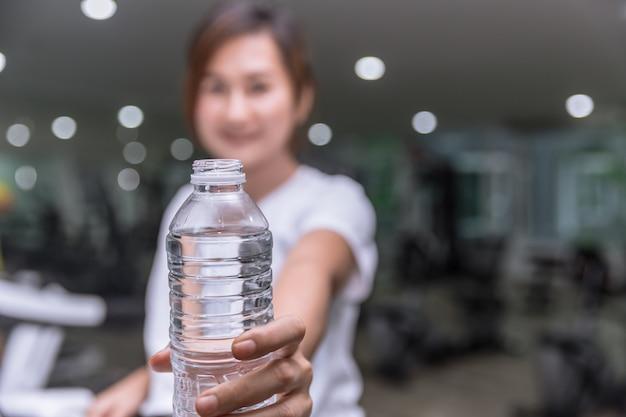 Chica fitness saludable sonrisa mano sostenga dar botella de agua potable en el club deportivo