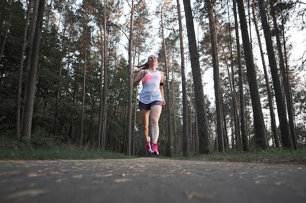 Chica flaca pelirroja blanca joven corriendo en el bosque de verano.