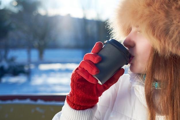 Chica flaca pelirroja, vestida con sombrero de piel de zorro y chaqueta blanca, tomando café para ir en un día frío de invierno.