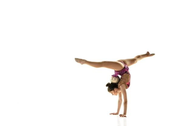 Chica flexible joven aislada en la pared blanca. modelo femenino adolescente como artista de gimnasia rítmica practicando con equipo. ejercicios de flexibilidad, equilibrio. gracia en movimiento, deporte.