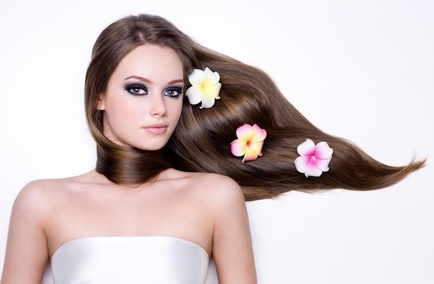 Chica con flores en su hermoso cabello largo y liso brillo
