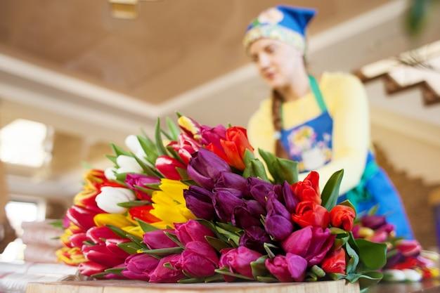 Chica florista empaca hermosos tulipanes en una florería en papel kraft