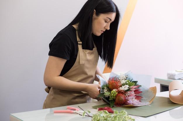Chica de floristería en delantal de arena en el trabajo crea un ramo de proteas