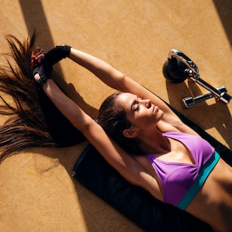 Chica de forma deportiva haciendo estiramiento completo mientras está acostado en la colchoneta con los brazos por encima de la cabeza y pesas cerca de ella.