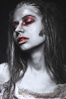 Chica en forma de zombies, cadáver de halloween con sangre en sus labios