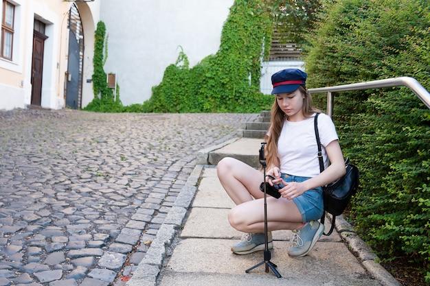 La chica fotógrafa se prepara para tomar fotos en la calle.