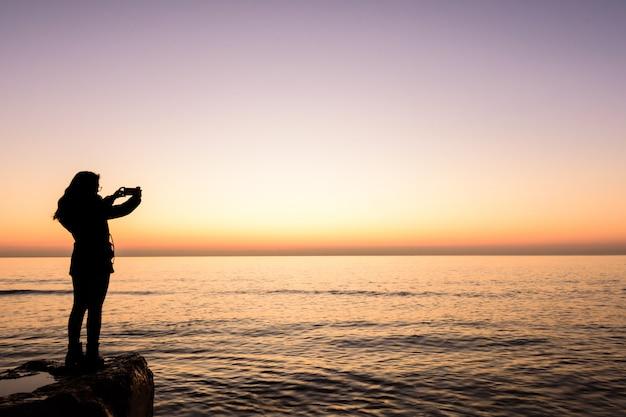 Chica fotografiando con el amanecer del teléfono móvil en la playa