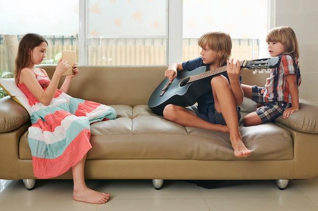 Chica fotografiando amigo con guitarra
