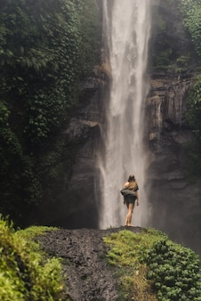 Chica se para frente a una enorme cascada