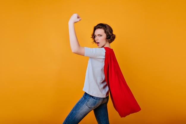 Chica fuerte en pantalones de mezclilla y camiseta azul posando con la mano arriba