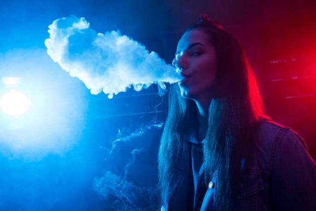 La chica fuma un cigarrillo y deja salir humo en un club nocturno.