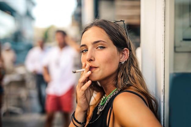 Chica fumando en la calle