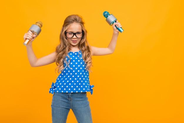 Chica con gafas agita sus manos con micrófonos en una pared naranja