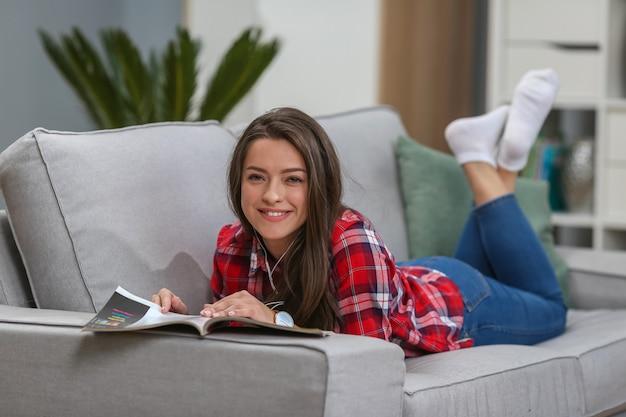 Chica con gafas escuchando música desde un teléfono inteligente con auriculares en la sala de estar en casa