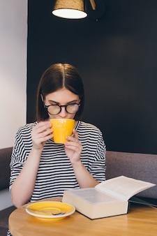 Chica con gafas leyendo un libro en una cafetería.