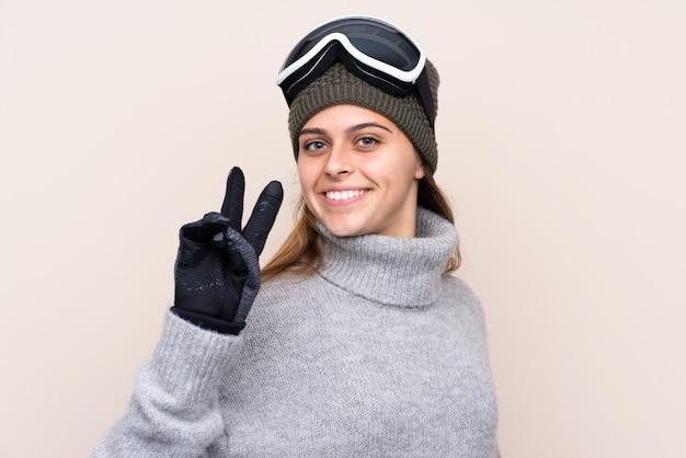 Chica con gafas de nieve sobre pared aislada