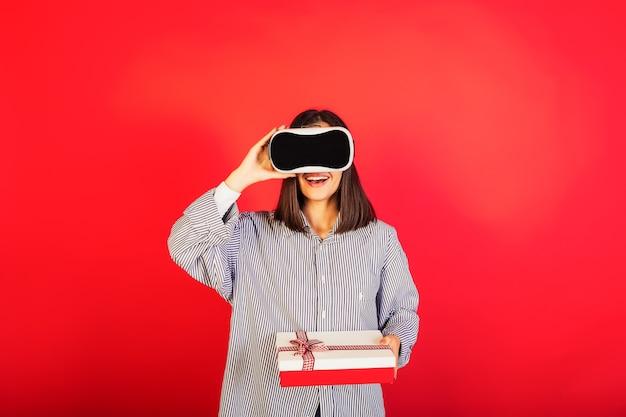 Chica con gafas de realidad virtual vr con caja de regalo sobre fondo rojo.