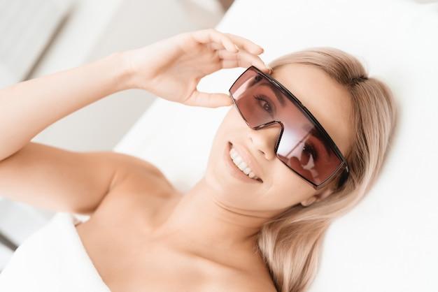 Chica con gafas en sala blanca esperando la depilación láser