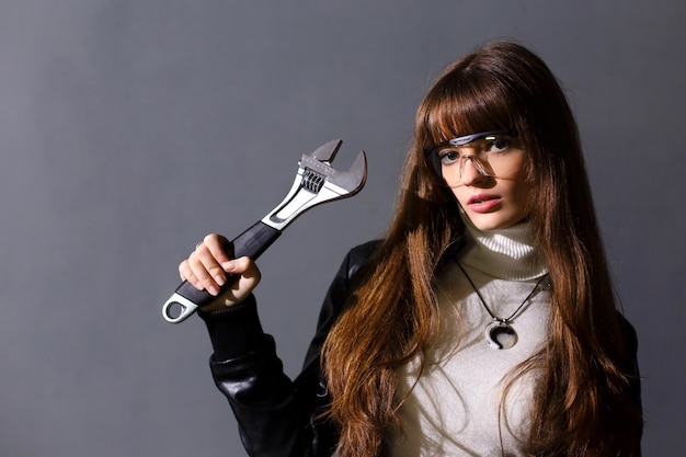 Chica con gafas de seguridad con llave ajustable sobre un fondo oscuro