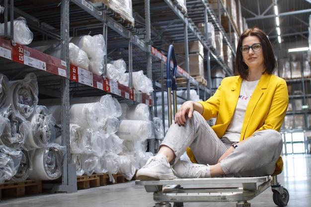 Chica con gafas sentado en un carrito de compras en una tienda en el almacén