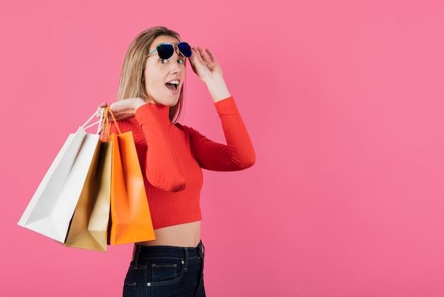 Chica con gafas de sol con bolsas de compras