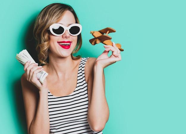 Chica en gafas de sol con dinero y aeroplano de madera.