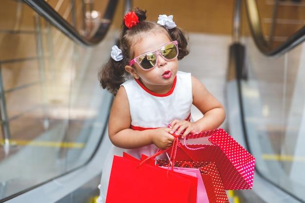 Chica con gafas de sol en la escalera mecánica del centro comercial con compras