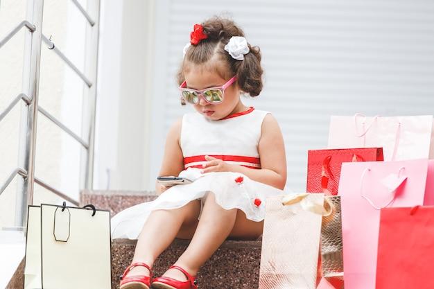 Chica con gafas de sol se sienta en los escalones del centro comercial con bolsas de colores