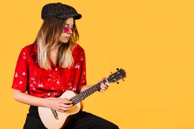 Chica con gafas tocando el ukelele