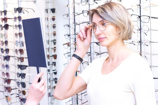 Chica de gafas para la vista. probando anteojos en una tienda de óptica. chica satisfecha