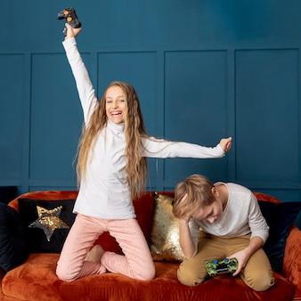 Chica ganando jugando videojuegos con su hermano