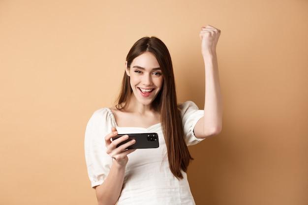 Chica ganando en teléfono móvil. mujer feliz levantando la mano y gritando sí con alegría, lograr el objetivo en la aplicación para teléfonos inteligentes, de pie en beige.