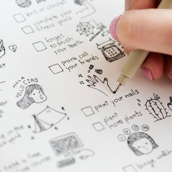 Chica garabateando y haciendo una lista de verificación en un cuaderno