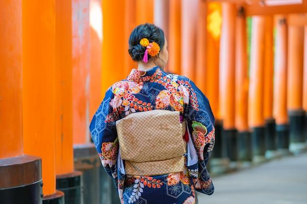 Chica geishas vistiendo kimono japonés entre la puerta de madera roja tori en el santuario fushimi inari en kioto,