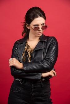 La chica genial con chaqueta de cuero negro y gafas de sol se ve estricta y exigente.