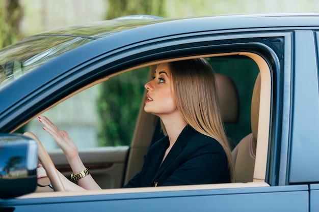 Chica gesto enojado mira en el espejo trasero en el coche trasero