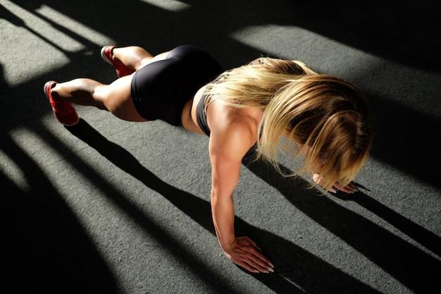 Chica en el gimnasio haciendo flexiones