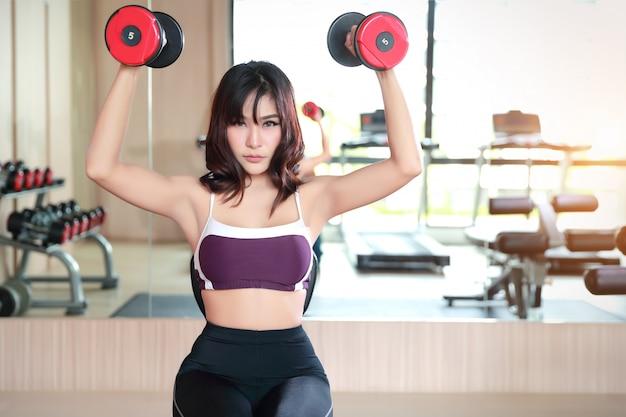 Chica de gimnasio levantando pesas y entrenamiento en el gimnasio