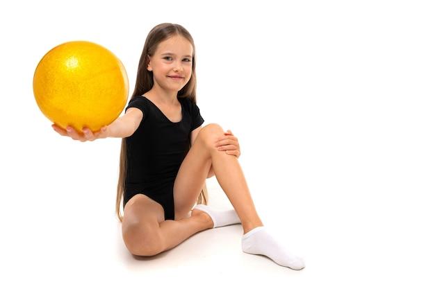 Chica gimnasta sentada en el suelo con pelota de gimnasia sobre un fondo blanco con espacio de copia.