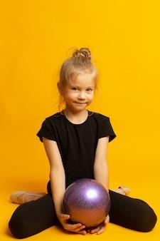 Chica gimnasta en trico negro de altura completa se sienta en una media página con una pelota deportiva aislada sobre un fondo amarillo
