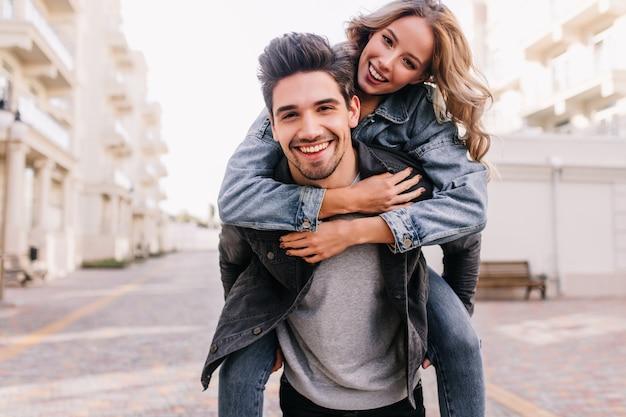 Chica glamorosa sentada en la espalda de su novio. retrato al aire libre de pareja caucásica despreocupada posando en la ciudad