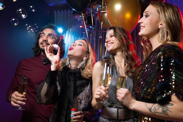 Chica glamorosa soplando pompas de jabón entre amigos con flautas de champán en la fiesta de cumpleaños
